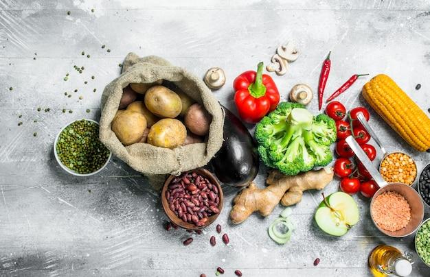 Zdrowe jedzenie. asortyment ekologicznych warzyw i owoców z roślinami strączkowymi na rustykalnym stole.