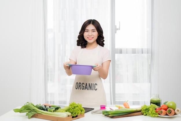 Zdrowe jedzenie. azjatycka kobieta gotuje w kuchni drewnianą łyżką