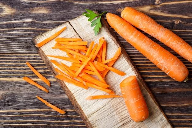 Zdrowe jedzenie - cała i pokrojona marchewka na drewnianym tle.