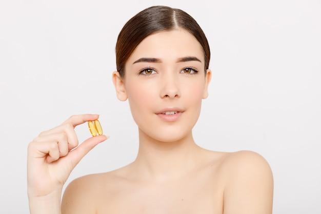 Zdrowe jedzenie dietetyczne. piękna uśmiechnięta młoda kobieta trzyma pigułkę z oleju rybnego w ręku. zbliżenie. biorąc kapsułkę. witaminy i suplementy diety