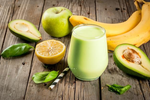 Zdrowe jedzenie. dietetyczne śniadanie lub przekąska. zielone koktajle z jogurtu, awokado, banana, jabłka, szpinaku i cytryny. na rustykalnym drewnianym stole z dodatkami. skopiuj miejsce