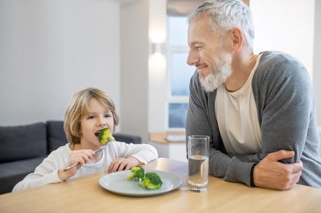 Zdrowe jedzenie. dojrzały mężczyzna i jego syn jedzą razem śniadanie