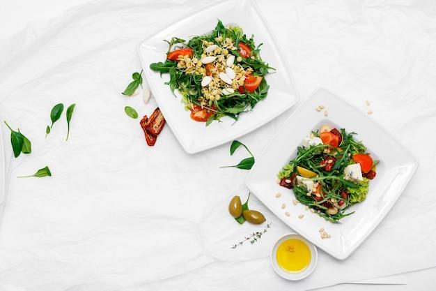 Zdrowe jedzenie. dwa białe talerze. sałatka z pomidorów, rukola, szpinak, oliwki, papryka. białe tło