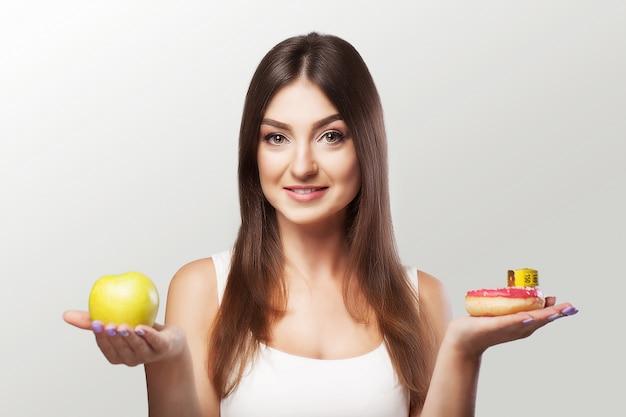Zdrowe jedzenie. kobieta traci na wadze. młoda dziewczyna waha się przed wyborem jedzenia lub sportu.
