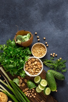 Zdrowe jedzenie koncepcja czystego jedzenia. zieleni warzywa, ziele, zboże i dokrętki na ciemnego tła odgórnym widoku ,.