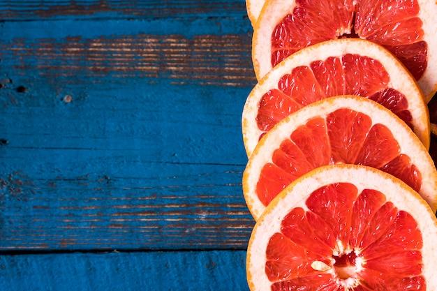 Zdrowe jedzenie koncepcja. wzór z świeżymi plasterkami czerwona pomarańczowa owoc na starym błękitnym drewnianym tle.
