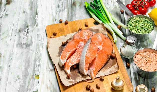Zdrowe jedzenie. łosoś z ekologicznymi warzywami, owocami i orzechami. na rustykalnym stole.