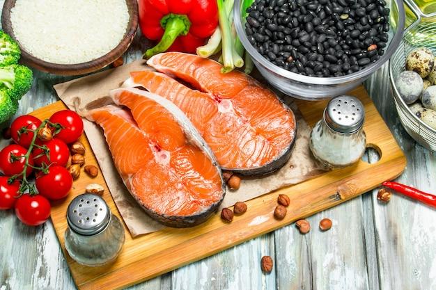 Zdrowe jedzenie. łosoś z miodem, orzechami i warzywami. na rustykalnym stole.