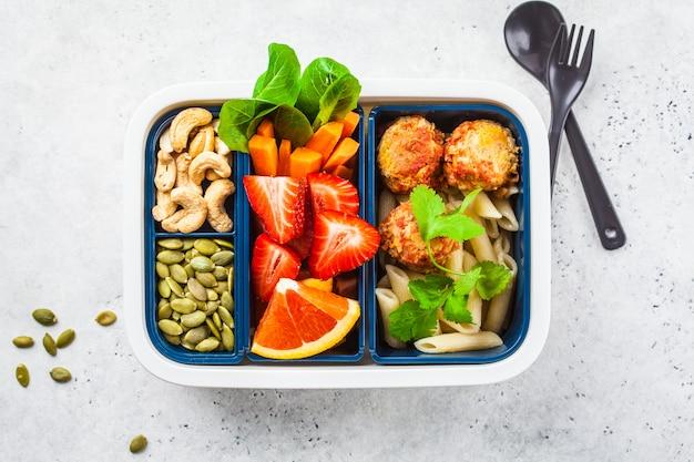 Zdrowe jedzenie lunch box. wegańska żywność: fasolowe klopsiki, makaron, warzywa, jagody, nasiona i orzechy w pojemniku