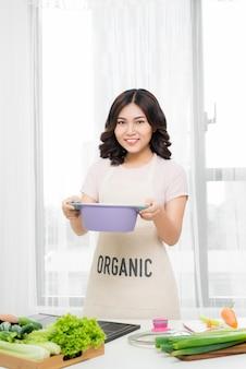 Zdrowe jedzenie. młoda azjatykcia kobieta gotowanie w kuchni w domu.