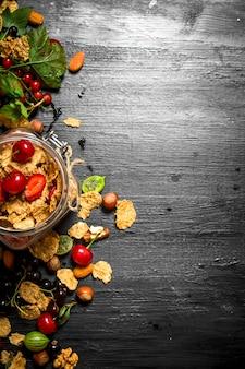 Zdrowe jedzenie. musli z leśnymi jagodami. na czarnym drewnianym stole.
