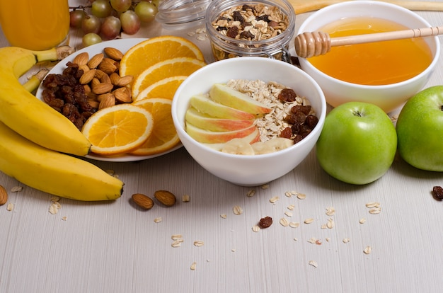 Zdrowe jedzenie. owoce, domowe granola, orzechy, płatki owsiane, miód, pomarańcza