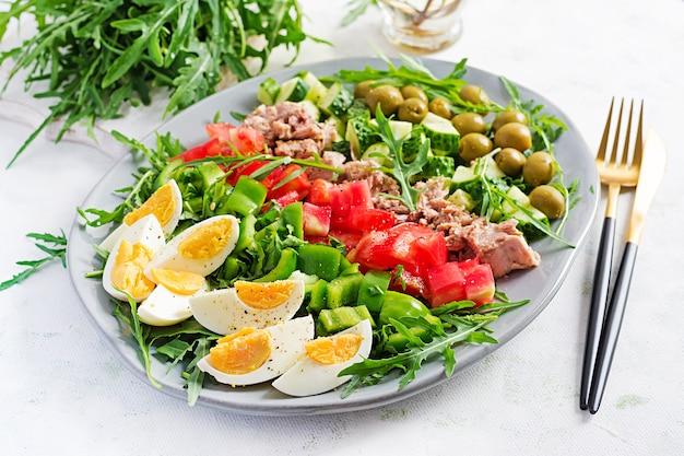 Zdrowe jedzenie. sałatka z tuńczyka z jajkiem, ogórkiem, pomidorami, oliwkami i rukolą. kuchnia francuska.