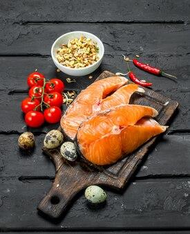 Zdrowe jedzenie. steki z łososia z pomidorami i przyprawami. na czarnym tle rustykalnym.