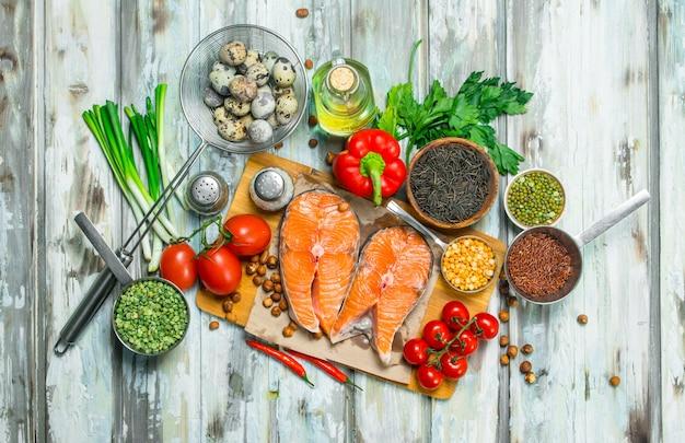 Zdrowe jedzenie. steki z łososia z żywnością ekologiczną. na rustykalnym.