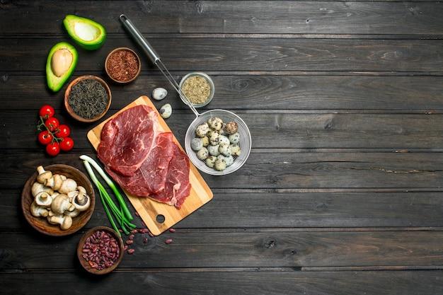 Zdrowe jedzenie. surowa wołowina z różnymi ekologicznymi przyprawami i żywnością. na drewnianym tle.