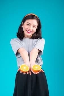 Zdrowe jedzenie. uśmiechający się piękny pinup asian girl gospodarstwa pomarańczowy na niebieskim tle.