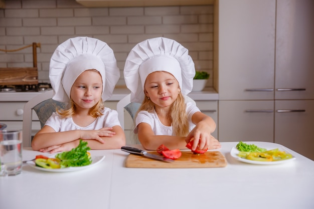 Zdrowe jedzenie w domu. szczęśliwa rodzina w kuchni. dwa słodkie śmieszne dzieci przygotowują warzywa.