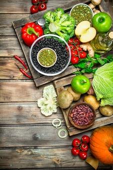 Zdrowe jedzenie. zdrowy asortyment warzyw i owoców z roślinami strączkowymi. na drewnianym stole.