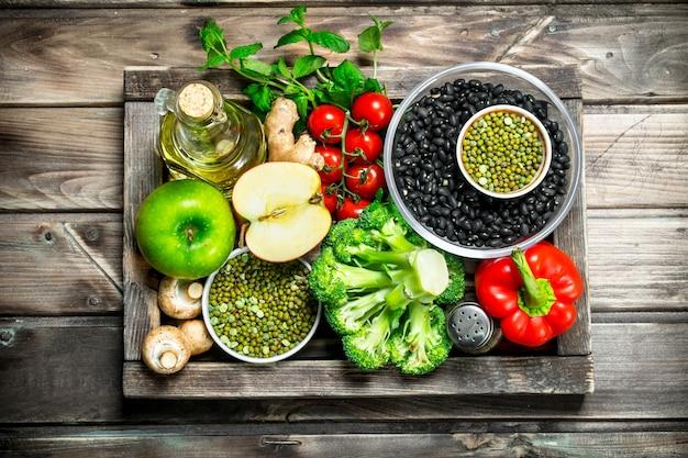 Zdrowe jedzenie. zdrowy asortyment warzyw i owoców z roślinami strączkowymi. na drewnianym tle.