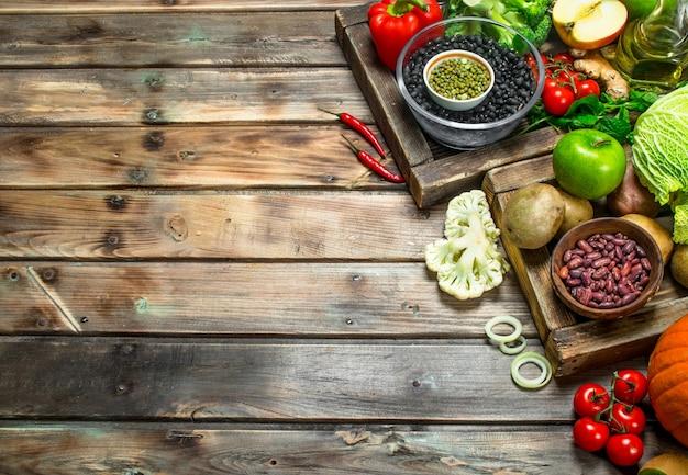 Zdrowe jedzenie. zdrowy asortyment warzyw i owoców z roślinami strączkowymi na rustykalnym stole.