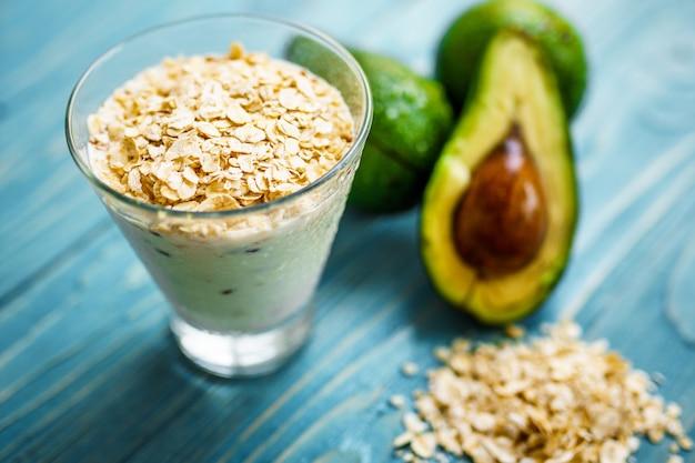 Zdrowe jedzenie. zielone koktajle z jogurtu, awokado, płatków owsianych na niebieskim drewnianym stole ze składnikami.