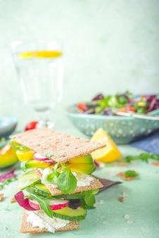 Zdrowe kanapki z chleba żytniego z chrupiącym pieczywem, twarogiem i świeżymi wiosennymi warzywami