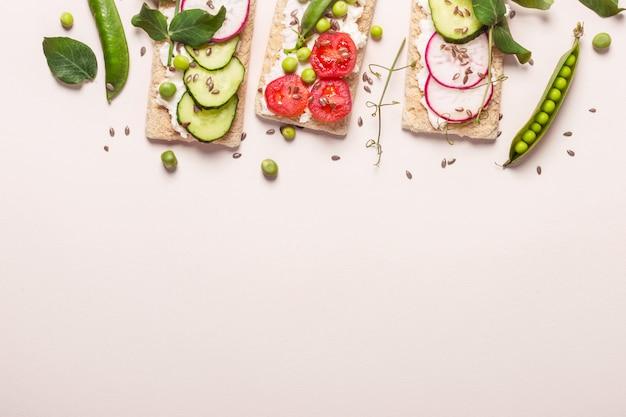 Zdrowe kanapki z miękkim serem i surowymi warzywami na chrupiącym chlebie.