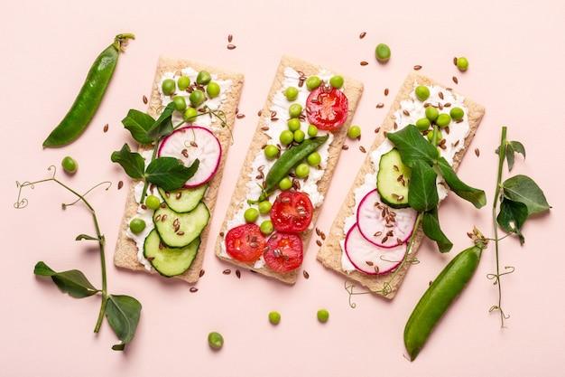 Zdrowe kanapki z miękkim serem i surowymi warzywami na pieczywie chrupkim.