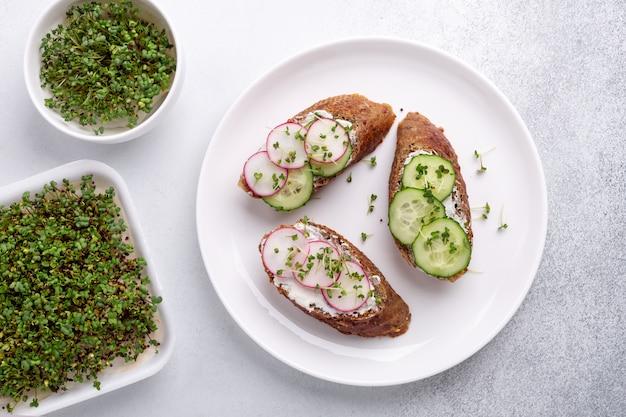 Zdrowe kanapki z pieczywem zbożowym, ricottą, ogórkiem, rzodkiewką i musztardą. mikro-zielone w misce. widok z góry. zdrowa przekąska
