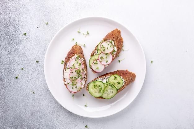 Zdrowe kanapki z pieczywem zbożowym, ricottą, ogórkiem, rzodkiewką i musztardą. na białym talerzu, widok z góry. zdrowa przekąska