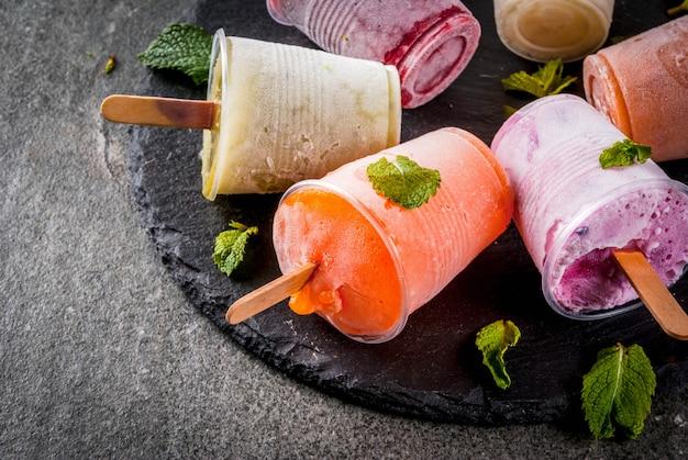Zdrowe letnie desery. lody popsicles. mrożone soki tropikalne, koktajle jagodowe. porzeczki, pomarańcza, mango, kiwi, banan, kokos, malina. na czarnym kamiennym stole, talerz