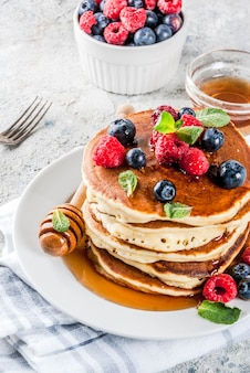 Zdrowe letnie śniadanie, domowe klasyczne amerykańskie naleśniki ze świeżymi jagodami i miodem, jasnoszary kamienny poranek