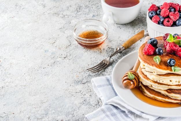 Zdrowe letnie śniadanie, domowe klasyczne amerykańskie naleśniki ze świeżymi jagodami i miodem, poranne li