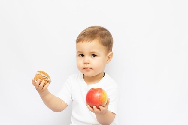 Zdrowe lub niezdrowe jedzenie mały chłopiec wybiera między ciastem a jabłkiem