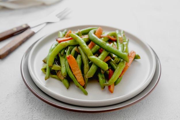 Zdrowe lub wegańskie jedzenie. gotowana zielona fasolka szparagowa i marchewka. zdrowa sałatka fasolka szparagowa i marchewki zamyka up.