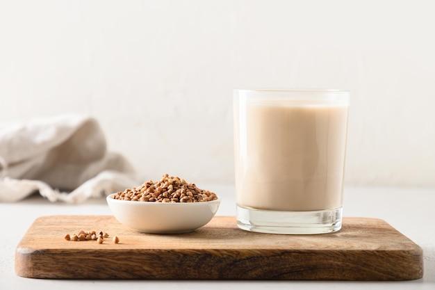Zdrowe mleko gryczane podawane ze zbożem w szklance do picia na drewnianej tacy