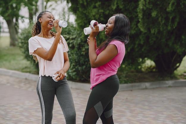 Zdrowe młode afrykańskie kobiety na zewnątrz w porannym parku. trening przyjaciół.