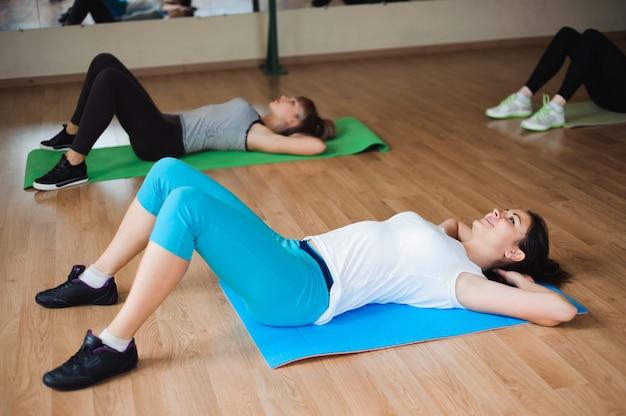 Zdrowe młode kobiety robi ćwiczeniu na matach dla sprawności fizycznej w gym.