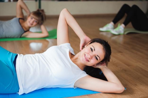Zdrowe młode kobiety robi ćwiczeniu na matach dla sprawności fizycznej w gym