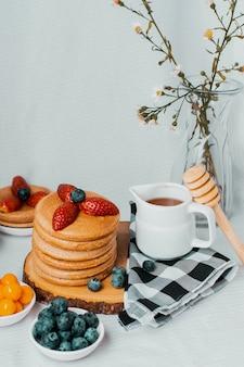 Zdrowe naleśniki z truskawkami jagodami miodem i chlebem świętojańskim na białym tle