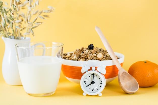 Zdrowe, obfite śniadanie. pieczona granola w misce, szklanka mleka, pomarańczy i budzik na żółtej powierzchni