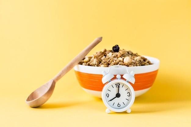 Zdrowe odżywianie. budzik przed pieczoną granolą z owsa, orzechów i rodzynek w misce i drewnianą łyżką na żółtej powierzchni