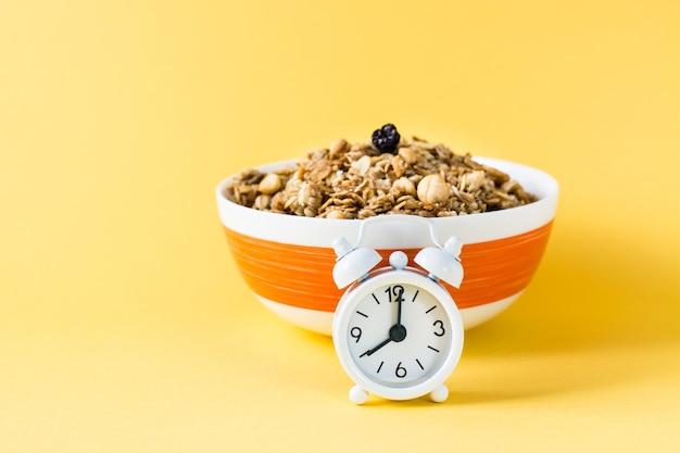 Zdrowe odżywianie. budzik przed pieczoną granolą z owsa, orzechów i rodzynek w misce na żółtej powierzchni