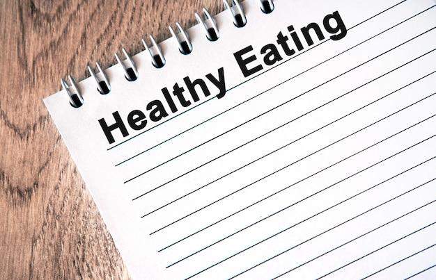 Zdrowe odżywianie - czarny tekst na białym notesie z liniami na drewnianym stole