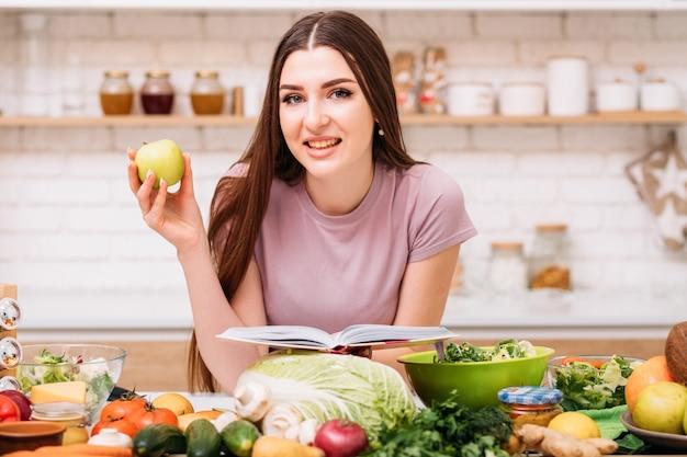 Zdrowe odżywianie. ekologiczne korzyści żywieniowe. młoda kobieta z jabłkiem i książką wegetariańskich przepisów.