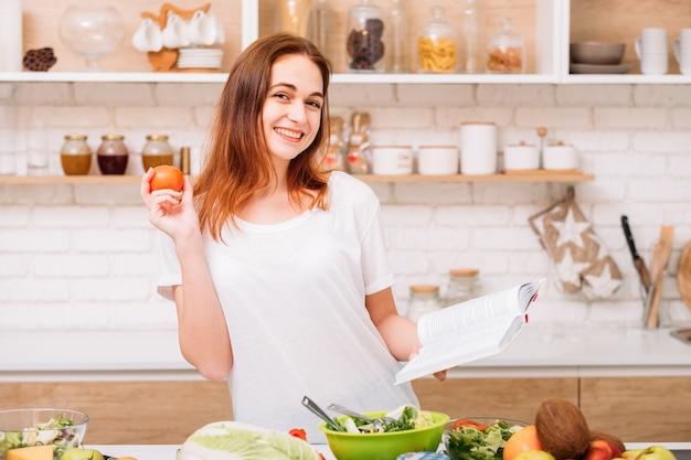 Zdrowe odżywianie. ekologiczne korzyści żywieniowe. uśmiechnięta młoda kobieta z pomidorem i książką wegetariańskie przepisy kulinarne.