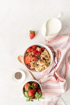 Zdrowe odżywianie i dieta. zdrowe śniadanie, płatki, świeże jagody i mleko w misce z miejscem na kopię, widok z góry na płasko