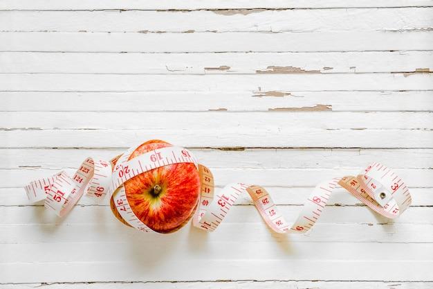 Zdrowe odżywianie i koncepcja diety. jabłczana i pomiarowa taśma na ośniedziałym białym drewnianym tle. widok z góry z miejsca na kopię.