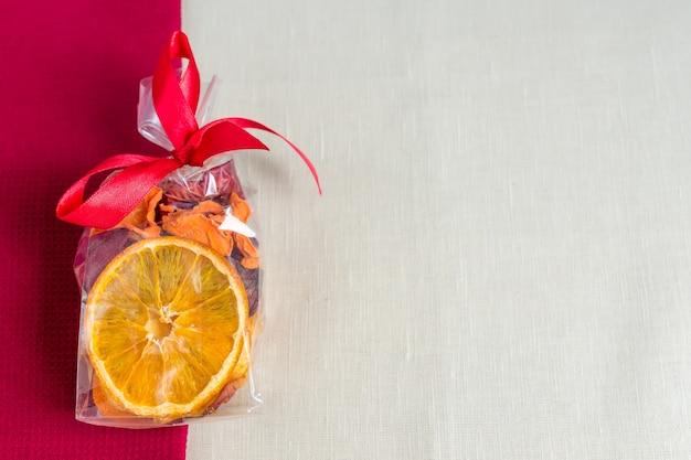 Zdrowe odżywianie organiczne. pokrojone i suszone jabłko, pomarańcza, marchew i buraki w opakowaniu prezent na tle włókienniczych.